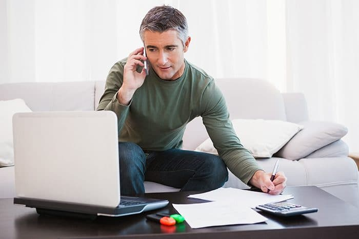 Man with laptop phoning and taking notes at home in the living room
