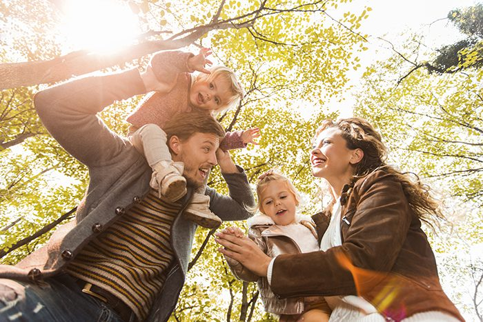 Low angle view of happy young parents having fun with their little girls in the forest and enjoying in autumn day.