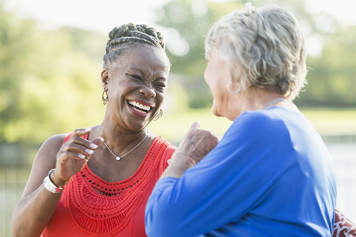 Two senior multi-ethnic woman, one Caucasian and the other African American, sitting in back yard by water enjoying each other's company. They are looking at each other, laughing.
