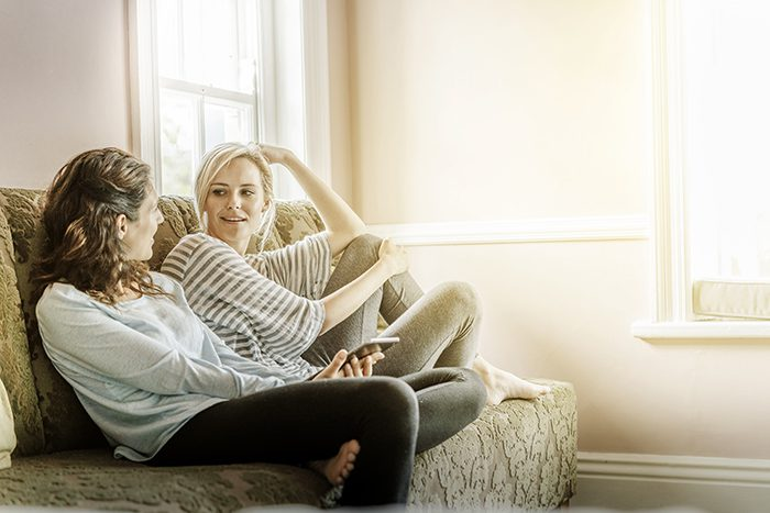 A photo of female friends gossiping on sofa. Happy young women looking at each other. Both are in casuals at home. They are in brightly lit room.