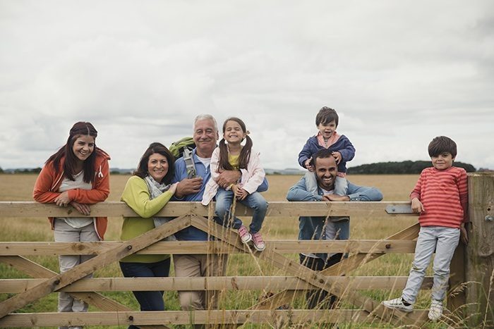 A three generation family leaning on a gate in the countryside in Northunmberland