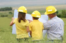 A Dad looking at blueprints for his dream house with his kids.
