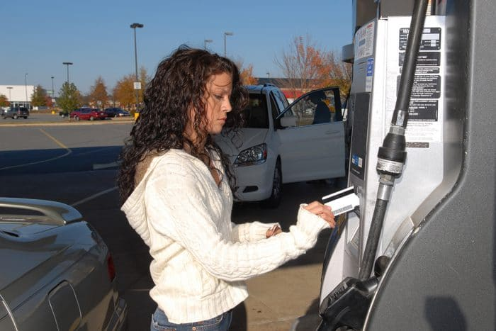 Young woman pays for gasoline at the pump with a credit card.