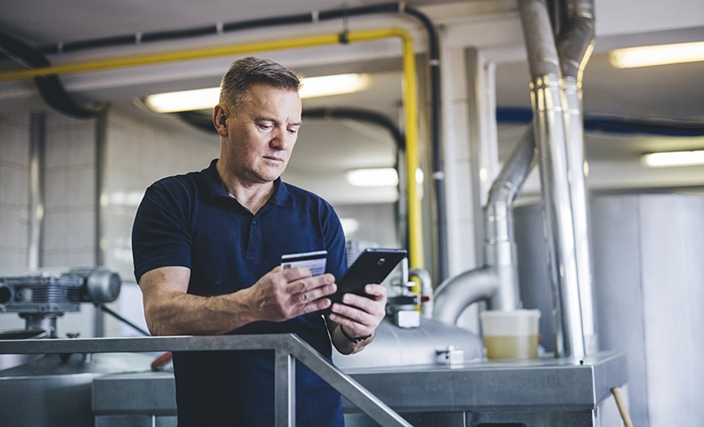 Brewer using smart phone while online shopping at brewery