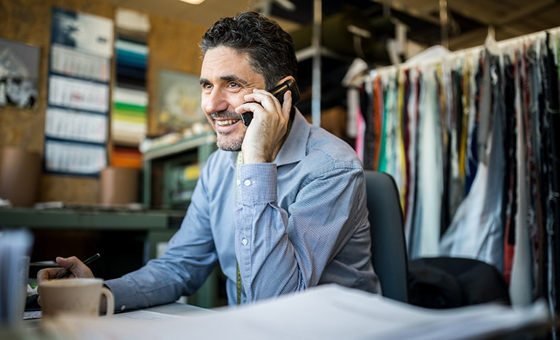 Fashion shop owner having telephonic conversation with client.