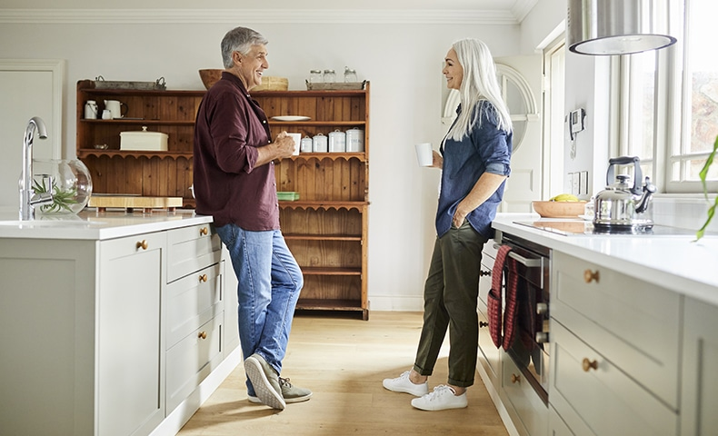 Mature couple talking while having coffee in kitchen