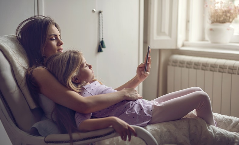 Mother and daughter in rocking chair using mobile phone.